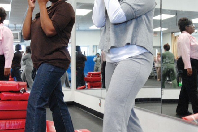 Zabrina Lowe with MEDDAC, left, and Army spouse Natasha Graham assume the ready position during a self-defense class Friday at the Family Fitness Center.