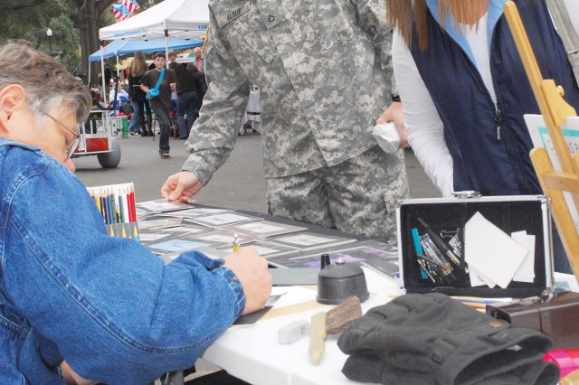 """PFC Dallas and Tiffany Alsup look at examples of the artwork of SFC(R) James Moore at Boots on Broadway.  Tiffany said they came out to the event because it was something fun to do on a Saturday.  """"It's a nice thank you,"""" Dallas said, """"and it's also a way to get to know what's around in the community."""""""