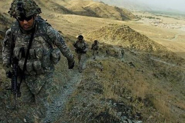 Soldiers in full battle gear travel a mountain trail in Afghanistan.