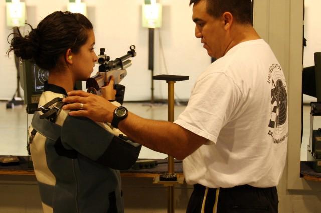 SSG Armando Ayala, U.S. Army Marksmanship Unit, shows the proper positioning to Breanna Kasl, a member of the Fort Benning Junior Rifle Club, at Pool Indoor Range.
