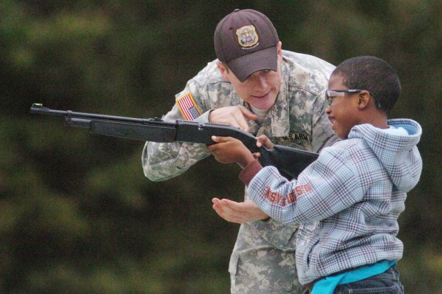 SGT David Sprecher, U.S. Army Marksmanship Unit, helps 7-year-old Keley Blackmon shoot a BB gun Saturday at Hook Range during Youth Sportsman Day.  Children shot archery, shotguns, and watched a hunting dog and a shotgun demonstration.