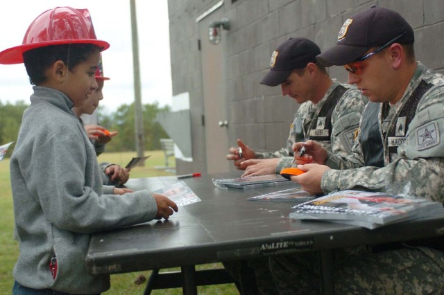 Bictor Gurrero, 7, gets an autograph from Olympic gold medalist SPC Vincent Hancock, right, and Olympic gold medalist SPC Glenn Eller, left.