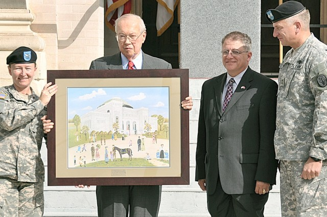 Col. Mary Garr, commander, U.S. Army Garrison (left) presents T.R. Fehrenbach with a reproduction of an original painting of the Gift Chapel as thank you for his participation in the centennial celebration. Maj. Gen. Russell Czerw (right), commander, Fort Sam Houston and Army Medical Department Center and School also presented Rep. Frank Corte Jr. with the chapel portrait.