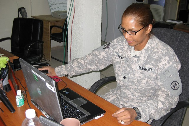 Spc. Yochanah Best, a paralegal specialist with the 395th Combat Sustainment Support Battalion, 15th Sustainment Brigade, works on her computer Oct. 23 at the Soldier Services Center here. Best became a U.S. citizen last year and now helps other Soldiers through the process as a paralegal specialist. (U.S. Army photo by Staff Sgt. Rob Strain, 15th Sustainment Brigade Public Affairs)