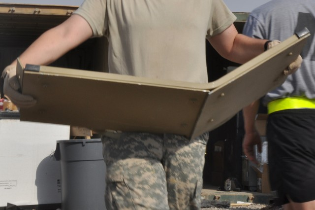 Spc. Josey Hunt, a information operations assistant with C Company, 2nd Battalion, 198th Combined Arms Brigade, and a Huntsville, Ala., native, carries a piece of scrap to separate excess equipment as part of Operation Clean Sweep, Oct. 23.