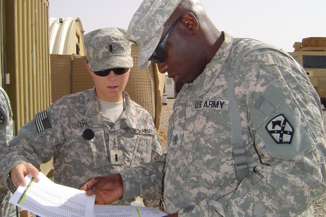 Sgt. Maj. Charles Wells, with the 15th Sustainment Brigade Support Operations, and 1st Lt. Meghan Flynn, the executive officer for Headquarters Company, discuss disposition of equipment during the company's turn in of non-essential equipment.