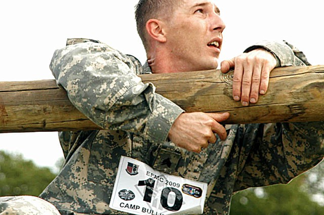 Sgt. John D. Hudgins, hospital education NCO at West Point, N.Y., Medical Department Activity, climbs a log barrier on the obstacle course during the Expert Field Medical Competition.