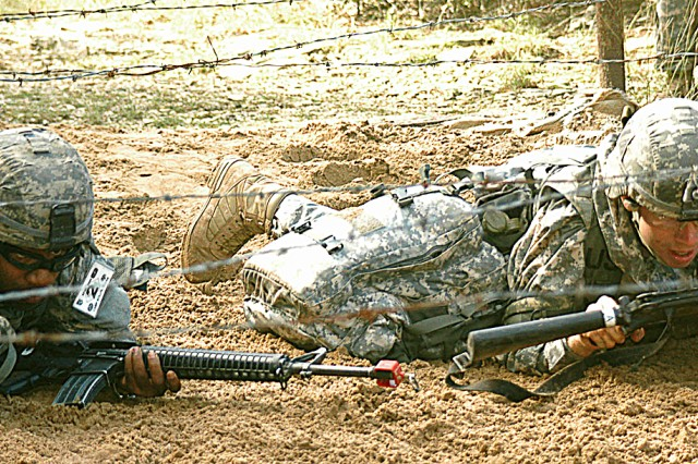 Sgt. Timothy D. Whitlock (left) and Sgt. Andrew L. Dishman crawl under a wire barrier during one of the combat medical lanes of the Expert Field Medical Competition. Whitlock and Dishman both are emergency care sergeants for 4th Brigade Combat Team, 3rd Infantry Division at Fort Stewart, Ga., and represented Forces Command in the competition.