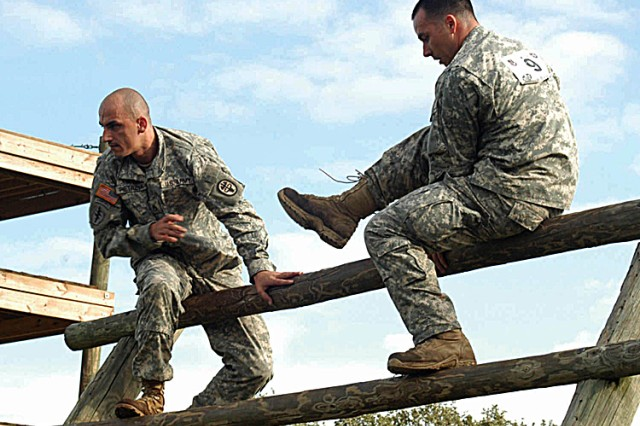 Staff Sgt. Bjoern Pietrzyk (left) and Sgt. Charles Smith climb a log barrier on the Expert Field Medical Competition obstacle course at  Camp Bullis. Pietrzyk, a healthcare specialist and Smith, a radiology specialist earned best scores in the combat medic lanes and road march, and were the overall winners for the competition.