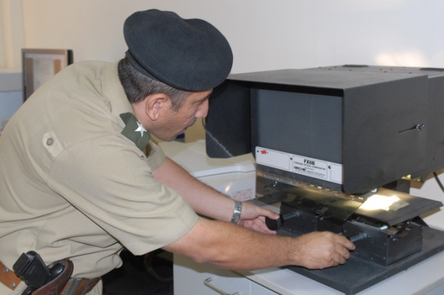 First Lieutenant Nazar Ihsan Chicho, an investigative officer at the Criminal Forensics Lab in Erbil, shows how to test for counterfeit bills during a tour of the facility for a group of 18 judges and lawyers Oct, 27. The goal of this tour was to expose the group to new technologies that investigative officers can use to find evidence.