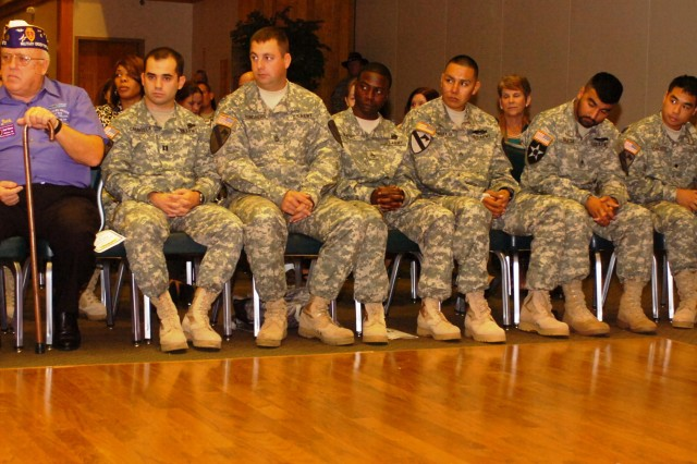 Jack Palmer, Commander of the Military Order of the Purple Heart, sits next to Purple Heart awardees Capt. Gregg Caravella, Sgt. 1st Class James Rundberg, Staff Sgt. Brent Mathis, Cpl. Tyrell Manakaja, Spc. Kevin Garcia, and Spc. Johnny Nguyen, from 1st Battalion, 5th Cavalry Regiment, 2nd Brigade Combat Team, 1st Cavalry Division during the Volunteer of the Month and Purple Heart recognition ceremony Oct 27, at the Phantom Warrior Club.