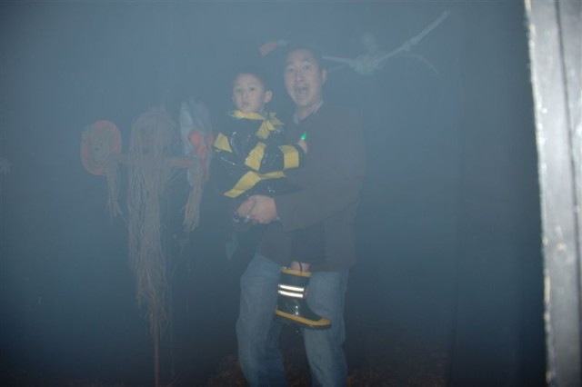 Dad plays scared while his son looks with suspicion as they make their way through USAG Schinnen haunted house during the garrisonAca,!a,,cs Trunk or Treat 2009 held Oct. 30.