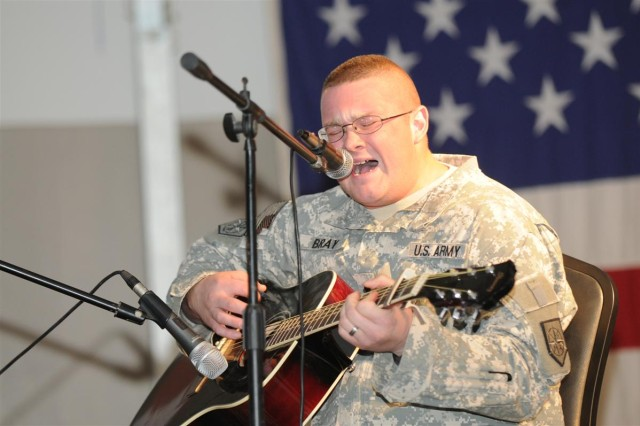"""Spc. Stephen L. Bray, a chemical, biological, radiological and nuclear specialist with the 248th Area Support Medical Company out of Marietta, Ga., performed a song he wrote called """"This Time,"""" during the talent show Oct. 24 at Morale, Welfare and Recreation east at Joint Base Balad, Iraq. Bray, a Kingston, Ga., native, said he has played guitar for roughly 11 years."""