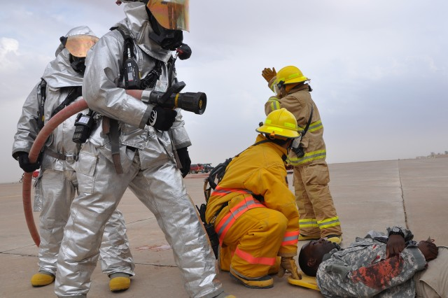 Q-West firefighters wearing protective gear react to a simulated helicopter crash during a mass casualty exercise here Oct. 28. (U.S. Army photo by Sgt. Matthew C. Cooley, 15th Sustainment Brigade public affairs)