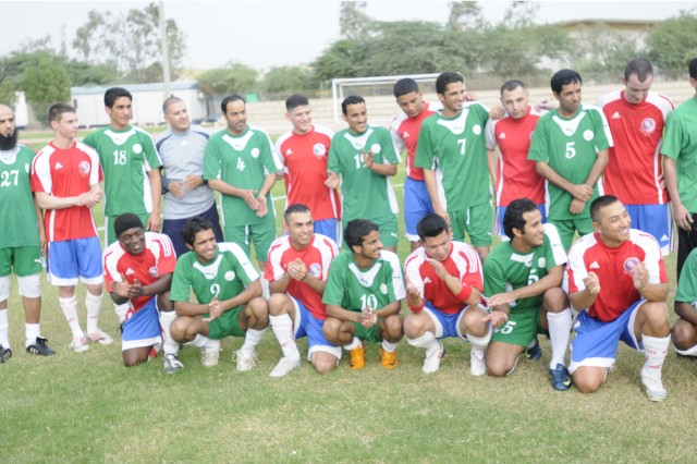 Soccer players from both the Kuwaiti National Guard Team (green) and the 1st TSC Team (red) smile during pre-game photos on Saturday at Camp Tahreer, Kuwait.