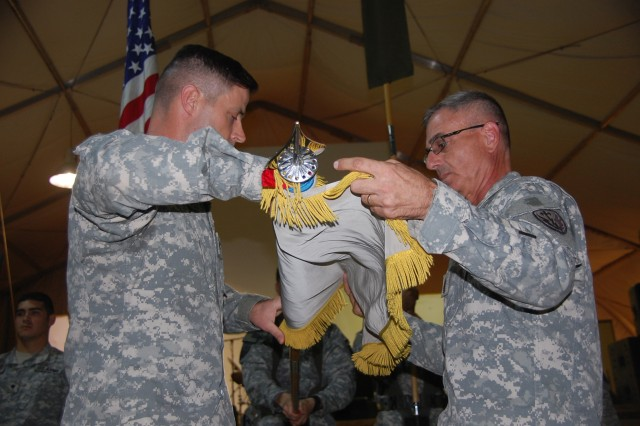 Commander of the 504th Battlefield Surveillance Brigade, Col. Robert Walters, Jr.,(left), and Command Sgt. Maj. Nicholas Rozumny, 504th BfSB's command sergeant major, case the brigade's colors in a transfer of authority ceremony at Contingency Operating Base Adder, Tallil, Iraq, on Oct. 28. The 504th BfSB, Fort Hood, Texas, has provided intelligence, surveillance and reconnaissance to  various brigade combat teams, three multi-national divisions and Multi-National Corps-Iraq during their 12-month deployment.