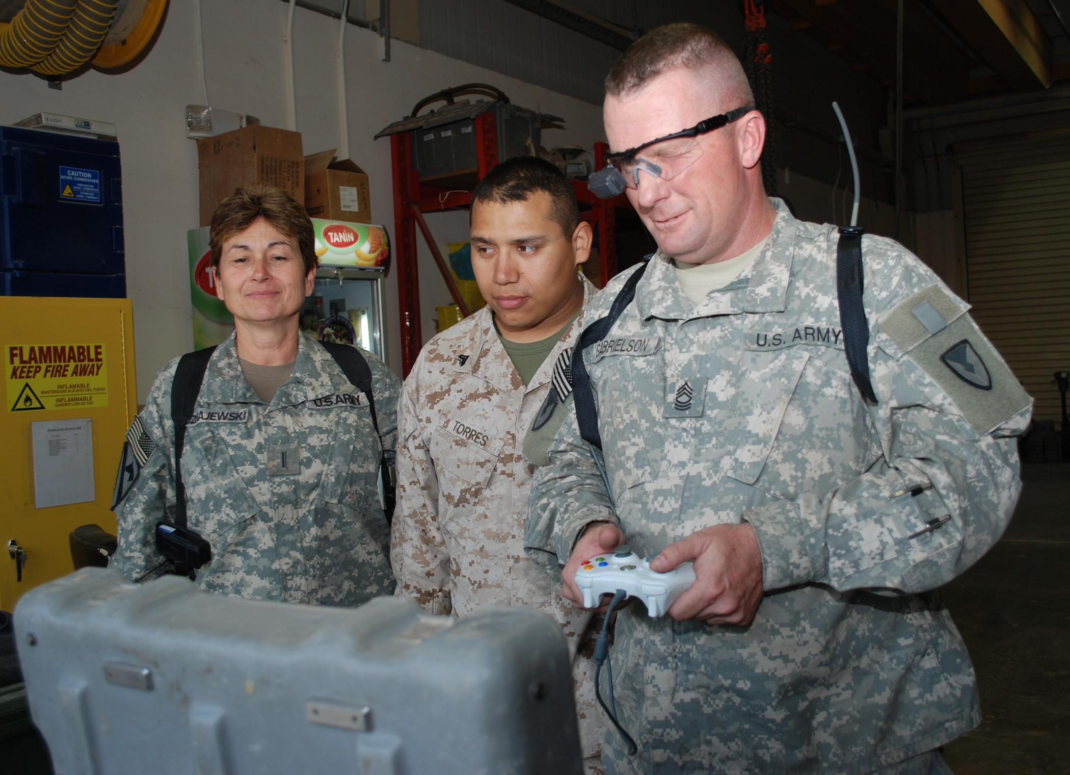 Chief Warrant Officer Mary T. Czuhajewski, commander of Logistics Support Element, Multi-National Force-Baghdad and Marine Cpl. Jose A. Torres look on as Master Sgt.  Kevin J. Gabrielson, 1st Battalion, 402nd Army Field Support Brigade, operates a PackBot using a  heads-up display at Joint Robotics Repair Detachment at Victory Base Complex, Baghdad, Iraq.