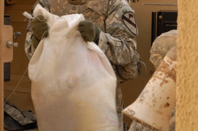 Pfc. Devin Brown, a Dallas, Ga., native and a cannon crew member with 3rd Battalion, 82nd Field Artillery Regiment, 2nd Brigade Combat Team, 1st Cavalry Division, helps unload bags of food and household goods during a humanitarian aid delivery in the Adallah District of Kirkuk city, Iraq, Oct. 31. Iraqi Policemen from the local community were on hand to help distribute the aid.