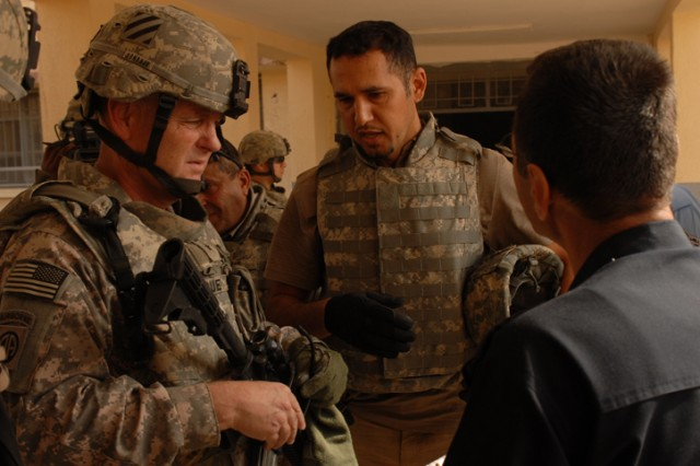 Brigadier General Patrick Donahue, the MND-N deputy commanding general for Maneuver, speaks through an interpreter to Col. Adnan Hameed Salaa, the police chief of the Adallah IP Station, during a humanitarian-aid delivery in the Adallah District of Kirkuk city, Iraq, Oct. 31. Brig. Gen. Donahue encouraged the police to keep up the good work.