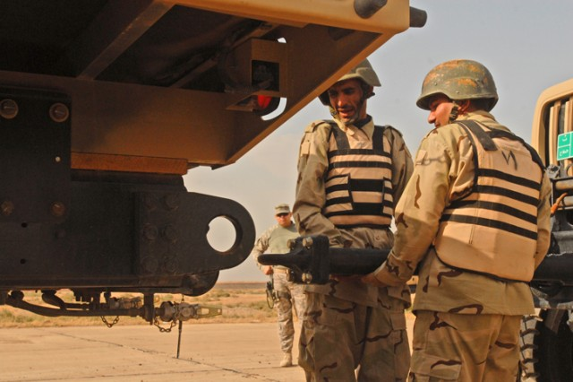 Iraqi Army Soldiers in the 12th MTR, 12th IAD, prepare to connect two vehicles during a truck rodeo competition at K-1 Military Base in Kirkuk, Nov. 1. These Soldiers, after attaching the vehicles, had to pull the truck forward in a safe manner to show that they had correctly performed towing procedure.