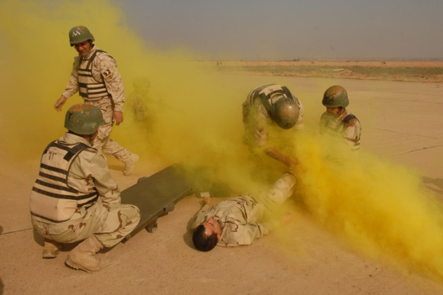 Iraqi Army Soldiers with the 12th MTR, 12th IAD, perform life-saving skills inside a fog of brightly colored smoke during a competition at K-1 Military Base in Kirkuk, Nov. 1. This competition was an opportunity for the Soldiers to test not only their medical skills, but also their skills as truck drivers and logisticians.