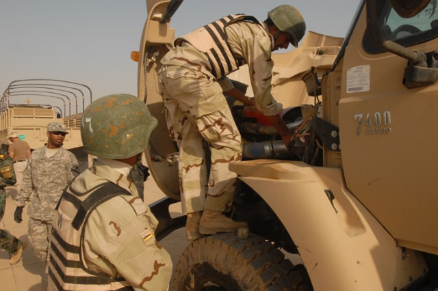 Iraqi Army Soldiers with the 12th MTR, 12th IAD, perform preventative maintenance checks on the engine of one of their transportation trucks during a competition at K-1 Military Base in Kirkuk, Nov. 1. This competition is known within the U.S. Army as a truck rodeo and was a chance to highlight the IA truck driving skills and knowledge.