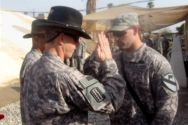 First Lieutenant Terrigno (right), a platoon leader with 3/82nd,  2BCT, 1st Cav. Div.,  salutes Lt. Col. Terry Cook, commander of 3/82nd FA, after he is awarded the Combat Action Badge for actions stemming from an Oct. 2 sniper attack in Kirkuk, Iraq.