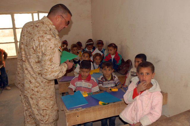 Second Lieutenant Abdul Hadi Faisal, an Iraqi officer with the 46th IA Bde., helps distribute school supplies to Iraqi children at the Jadeeda Primary School near Hawijah in the Kirkuk province of Iraq, Oct. 28. The supplies were provided by Families of Soldiers from 1/8th Cav., 2BCT, 1st Cav. Div.
