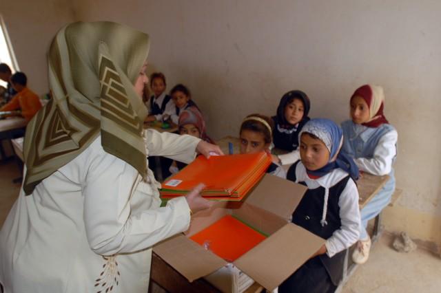An Iraqi school teacher helps distribute school supplies to Iraqi children at the Jadeeda Primary School near Hawijah in the Kirkuk province of Iraq, Oct. 28. The supplies were provided by Families of Soldiers Families of Soldiers from 1/8th Cav., 2BCT, 1st Cav. Div.