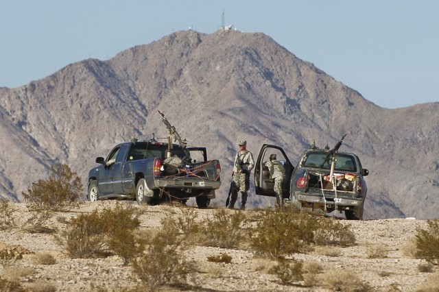FORT IRWIN, Calif --  Soldiers from the Technical Truck Squad, 2nd Platoon, Delta Company, 1st Squadron, 11th Armored Cavalry Regiment, take in the view of Tiefort Mountain after their unit's Mechanized Infantry Battalion, Opposition Force Qualification here Oct. 21, 2009.