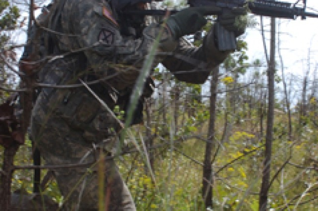 Spc. David Loremayo, Troop B, 3rd Squadron, 89th Cavalry Regiment, 4th Infantry Brigade Combat Team, 10th Mountain Division, advances through heavy brush toward opposing forces after taking fire during a squadron field training exercise at Castor 1 and 2 training areas, Sept. 23.