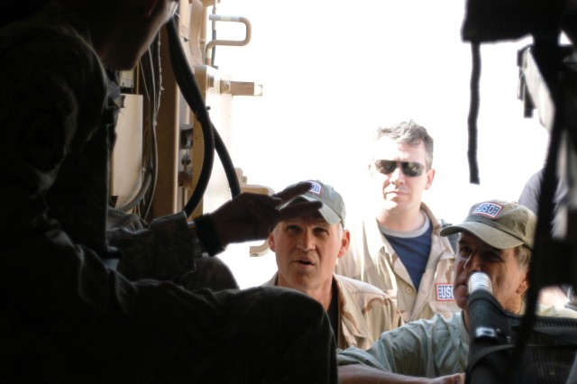 CONTINGENCY OPERATING LOCATION Q-WEST, Iraq - Sgt. Seth A. Bloodworth (left), of Lake Cormorant, Miss., and truck commander with A Company, 2nd Battalion, 198th Combined Arms out of Hernando, Miss., describes the Heavy Armored Ground Ambulance, a medical evacuation variant of the Mine-Resistant, Ambush-Protected truck, to Chip Bok (left, facing), Tom Richmond and Garry Trudeau, three of five cartoonists who visited Q-West Oct. 20 to meet and draw for the troops. The tour was sponsored by the USO and the National Cartoonists Society.
