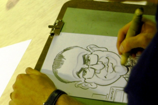 CONTINGENCY OPERATING LOCATION Q-WEST, Iraq - Satirical cartoonist Tom Richmond, Mad Magazine, draws a caricature of a Soldier during a visit here Oct. 20. Richmond was among five popular cartoonists and caricaturists who entertained troops at the main dining facility. Along with Richmond, Garry Trudeau, Jeff Keane, Stephan Pastis and Chip Bok spent from 11 a.m. to 1 p.m. talking with and drawing for long lines of service members.