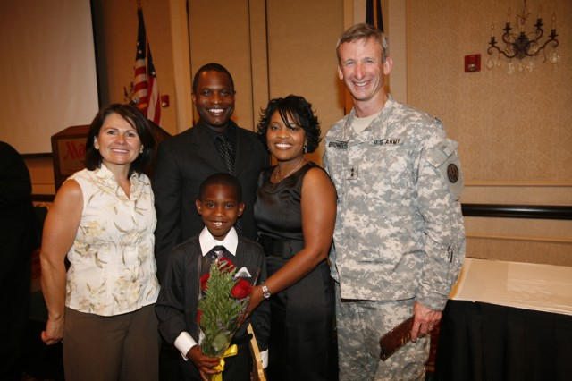 Texas state Secondary Teacher of the Year and Army spouse Yushica Walker, second from the right, beams her excitement after being chosen Secondary Teacher of the Year for her district at a banquet in May.  Pictured with her are, from the left, Mrs. Glenda Bromberg (wife of the Fort Bliss commander), son Johnnie Walker III, husband Maj. Johnnie R. Walker, II, and Maj. Gen. Howard B. Bromberg, commanding general of Fort Bliss, Texas.