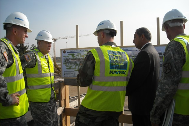 U.S. Army Gen. Carter F. Ham (2nd from left), commanding general of U.S. Army Europe and 7th Army listens to Cmdr. William Whitmire (center), U.S. Navy resident officer-in-charge of construction for the U.S. Naval Facilities Engineering Command Europe and Southwest Asia during a status brief boots on the ground given by Kambiz Razzaghi, chief of Transformation Construction Management Office. Ham was accompanied by Maj. Gen. William B. Garrett III, U.S. Army Africa commander (left) and welcomed  by USAG Vicenza Commander Col. Erik Daiga (right)