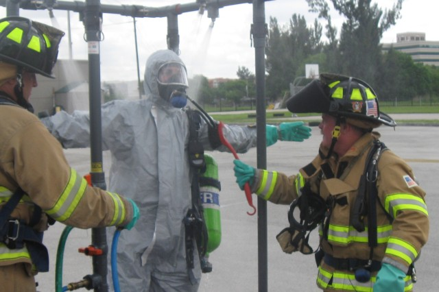 Following his entry into the contaminated zone to determine the type of chemical released, a Miami-Dade Fire Rescue hazardous materials specialist goes through the decontamination process.