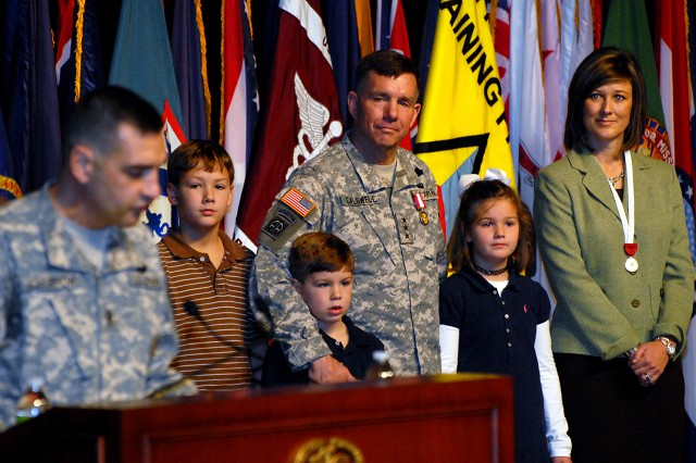 Combined Arms Center and Fort Leavenworth Commander Lt. Gen. William Caldwell IV, joined by his wife, Stephanie, and children Will, Hudson and Anna Katherine, listens to the farewell message from CAC Command Sgt. Maj. Philip Johndrow during Caldwell's departure ceremony Nov. 2 at the Lewis and Clark Center.