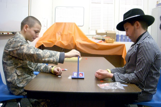 """Kendall Ingram (left), 10, son of Michael and Jan Ingram, religious education coordinator for the Fort McPherson post chapel, and Liam Lacey, 12, son of Maj. Teresa Walker, training officer, U.S. Army Reserve Command, play a game of """"Connect Four"""" during the U.S. Army Garrison Chapel Fall Festival Saturday at the Fort McPherson Garrison Chapel. The festival, held as an alternative to a traditional Halloween celebration, offered fun, food and games for Kendall, Liam and other children from Fort McPherson and Fort Gillem."""