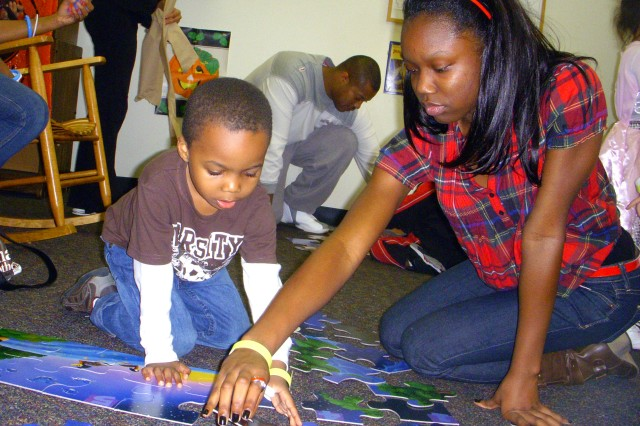 Siblings Antonio (left) and Alexis Scott work together to complete a puzzle. Antonio, 5, and Alexis, 16, attended the festival with their grandfather, retired sergeant major Edward Scott.