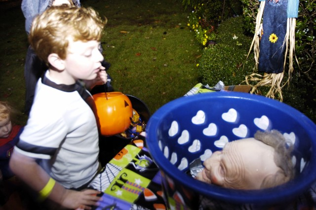 """Thomas Stephenson, 5, son of Laura Stephenson, Fort McPherson Child and Youth Services pre-kindergarten teacher, peers into the """"Candy for Adults"""" basket while trick-or-treating, ready to see what type of candy might be inside. Rather than treats, the basket had a scare in the form of Chap. (Col.) Michael Tarvin's masked head. Tarvin is a U.S. Army Forces Commandchaplain. Thomas and other children throughout Fort McPherson enjoyed a night full of thrills and candy during trick-or-treating festivities Saturday."""
