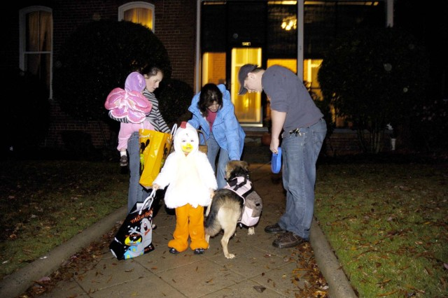Halloween was a family affair for the Baker family, including their dog, Cookie, seen getting a treat from Joanne Vangjel, wife of  Maj. Gen. Peter Vangjel, deputy commanding general, Third Army/U.S. Army Central (USARCENT). The Baker family includes Spc. Elizabeth Baker (left), a mechanic with Headquarters and Headquarters company, Third Army, daughter Haley (in pink), 1, son, Rylan (in chicken outfit), 2, and their father, Brok Chase (right), a student at Central Texas College.