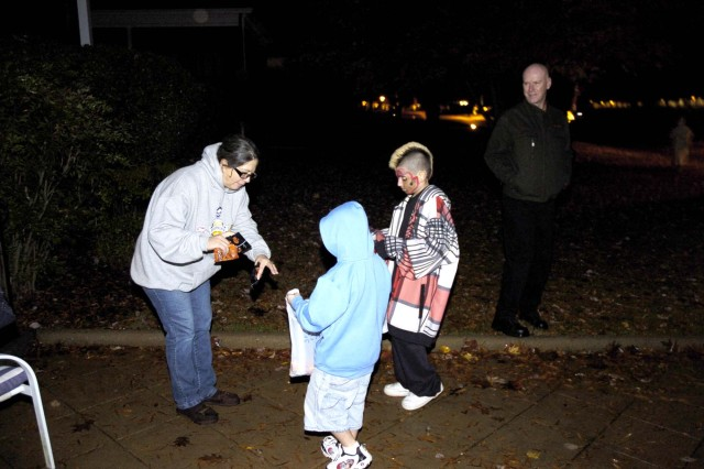 Left: Alice Nuttall, wife of Maj. Gen. Jim Nuttall (right), deputy commanding general, First Army, hands out candy to Hector Uresti Jr. (in blue), 7, and Joshua Sanchez, 11. The two were out with Uresti's father, Hector Uresti Sr., a Reams Enterprises maintenance man on Fort McPherson.