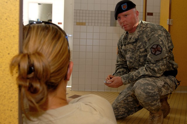"""Pfc. Steven Chiaravalle, a military police officer with the Fort Irwin U.S. Army Garrison Military Police Company, interviews a """"victim"""" of a sexual assault during a training event Oct. 24 of Fort Irwin. The victim was portrayed by Deputy Amy Puzio, of the Los Angeles County Sheriff's Department. The scenario took place at Fort Irwin Middle School and demonstrated interview procedures for sexual assault crimes."""