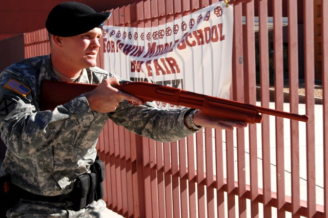 """Sgt. Benjamin Robinson, a team leader military police officer with the Fort Irwin U.S. Army Garrison Military Police Company, approaches an entrance to Fort Irwin Middle School with a """"dummy"""" shotgun during a training event Oct. 25. The scenario involved responding to an emergency call about suspects with weapons within the school."""