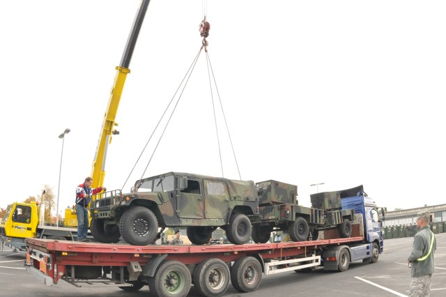 Sgt. Mark Setser with the 21st Theater Support Command oversees the loading of rolling stock at the U.S. Army Garrison Wiesbaden's Installation Staging Area on Wiesbaden Army Airfield in preparation for the 1st Armored Division's deployment to Iraq in early 2010.