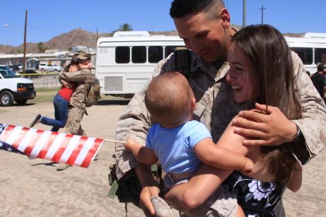 Capt. Justin Sharpe, the executive officer for Comanche Company, 3rd Light Armored Reconnaissance Battalion, hugs his wife and looks in amazement on how big his 8-month-old son has grown throughout the battalion's deployment to Iraq during their homecoming at Victory Field Sept. 8.