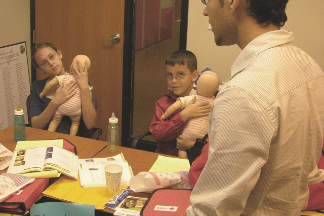 Red Cross instructor Jorge Medina talks to the class about holding infants correctly.