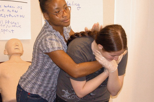 Students practice relieving a choking victim by removing foreign objects through a sharp blow to the upper back.