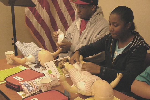 Students of the Garrison Family and Morale, Welfare and Recreation Offices Babysitting and CPR class learn about changing infants and also about saving lives.