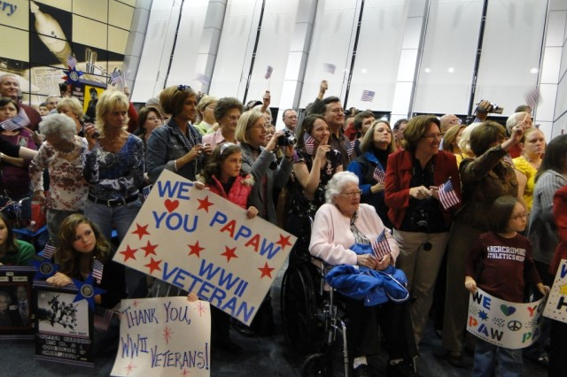 A crowd of hundreds cheers for returning World War II veterans as Ola Mae Kakac, in wheelchair, waits patiently for her husband's return from the Oct. 24 Tennessee Valley Honor Flight. Her husband is Fillmore Kakac, whose brother's burial flag was part of the Honor Flags Presentation at the World War II memorial.